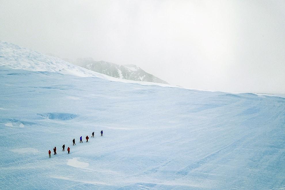 Een groep gasten hiket op het blauwige ijs tijdens een excursie naar de Drake Icefall op een bewolkte dag.